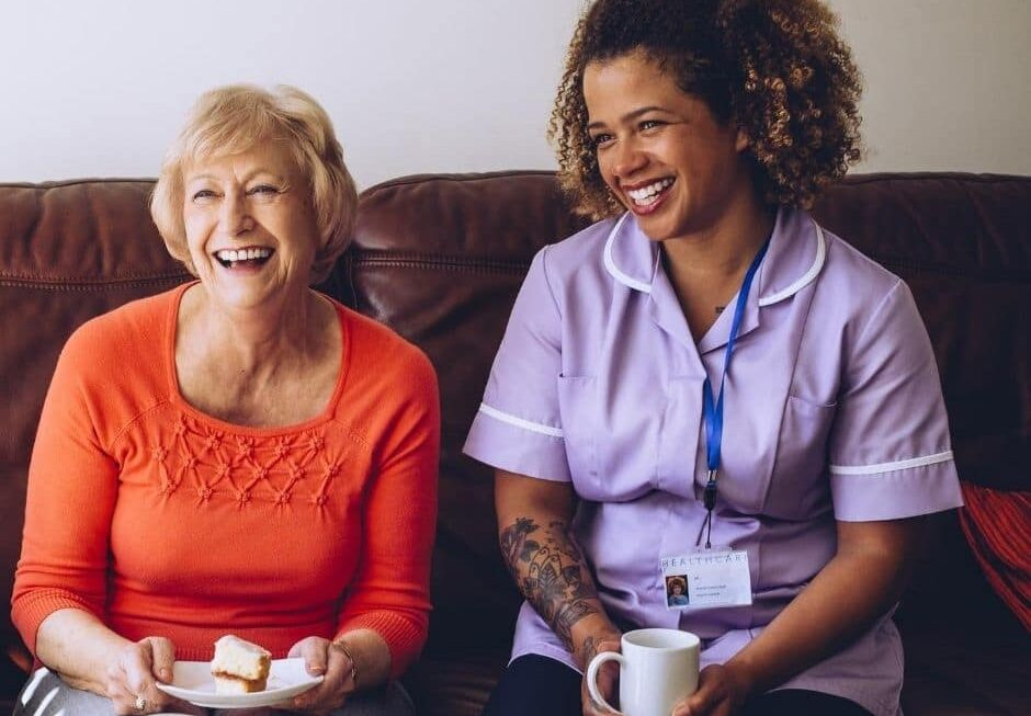 Carer laughing with elderly client