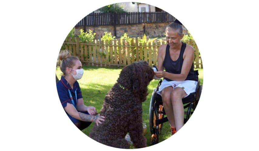 Carer out in the garden with client playing with her dog