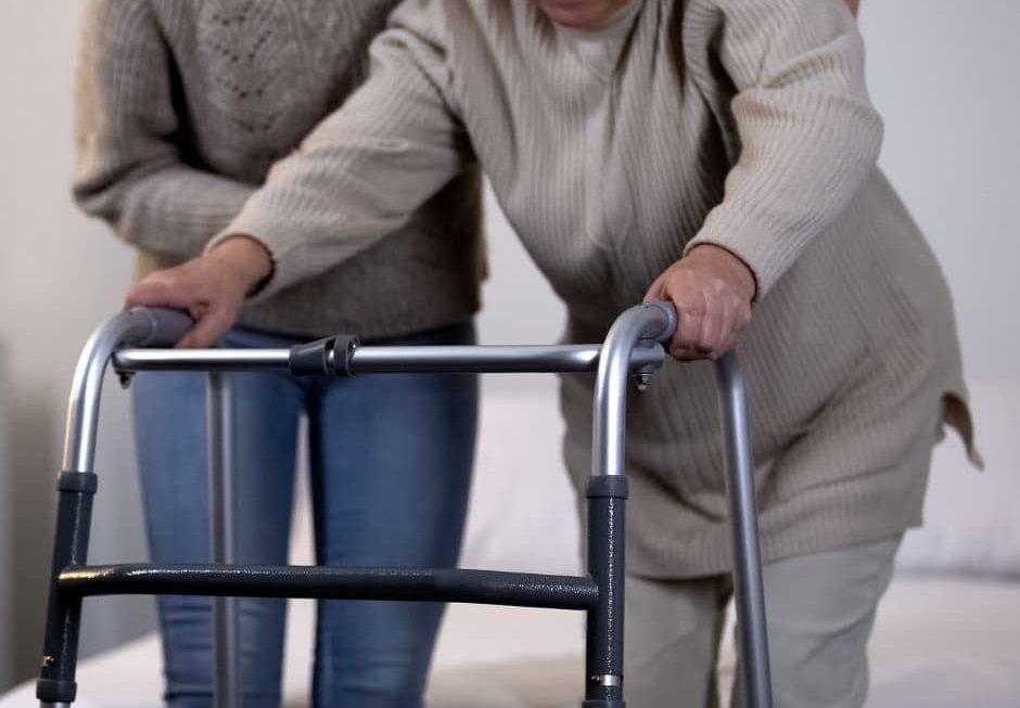 Elderly lady with walking frame and woman helping her
