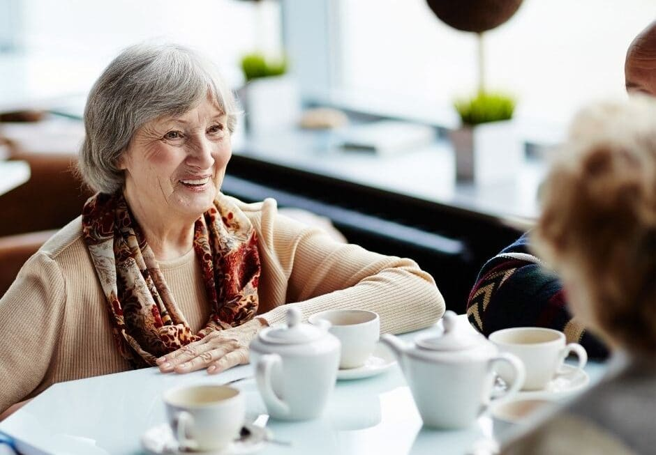 A group of elderly ladies sit around a table with tea cups and teapots