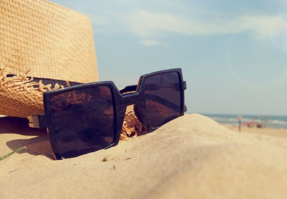 Straw hat with glasses placed on the beach