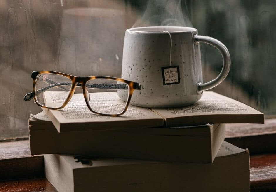Pile of books with glasses and hot cup of tea placed on top in front of a window on a rainy day